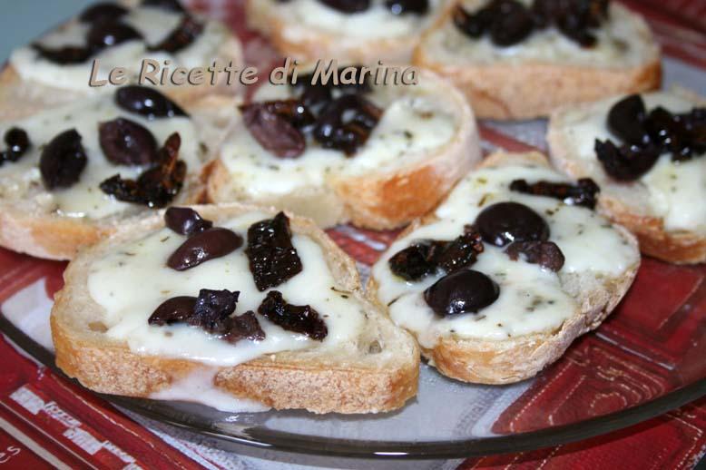 Bruschette con formaggio olive e pomodori secchi